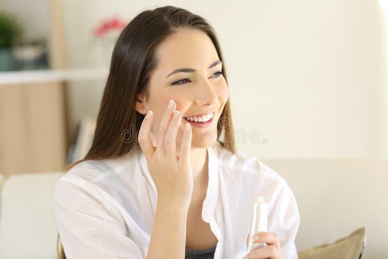 Γυναίκα ομορφιάς που εφαρμόζει moisturizer την κρέμα στο πρόσωπο στοκ εικόνες με δικαίωμα ελεύθερης χρήσης