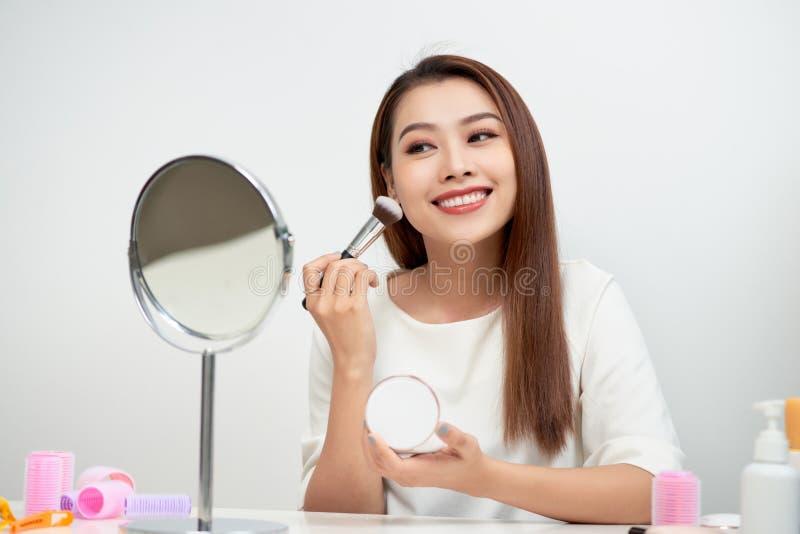 Γυναίκα ομορφιάς που ισχύει makeup Όμορφο κορίτσι που κοιτάζει στον καθρέφτη και που εφαρμόζει το καλλυντικό με μια μεγάλη βούρτσ στοκ φωτογραφία με δικαίωμα ελεύθερης χρήσης
