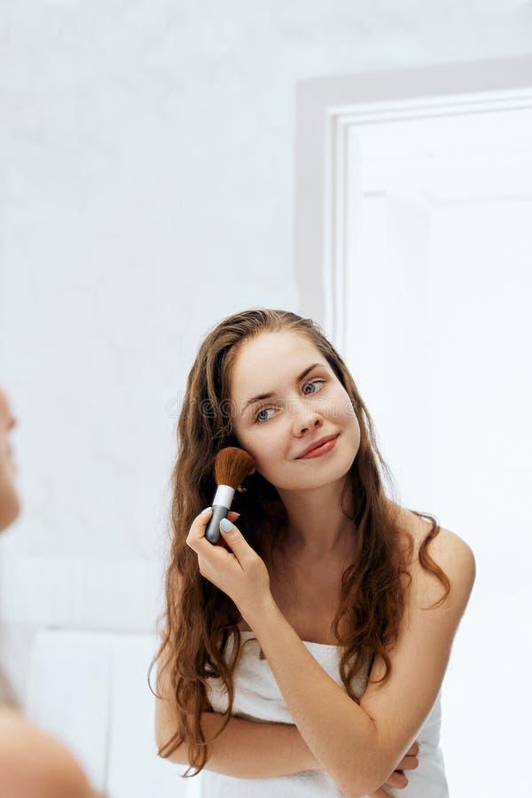 Γυναίκα ομορφιάς που ισχύει makeup Όμορφο κορίτσι που κοιτάζει στον καθρέφτη και που εφαρμόζει το καλλυντικό με μια μεγάλη βούρτσ στοκ φωτογραφίες με δικαίωμα ελεύθερης χρήσης