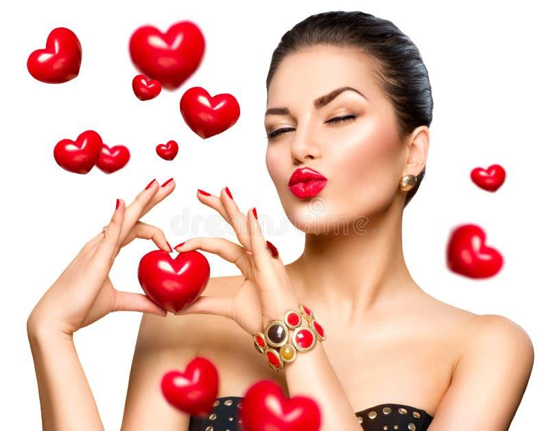 Γυναίκα ομορφιάς που παρουσιάζει κόκκινη καρδιά στα χέρια της στοκ φωτογραφία