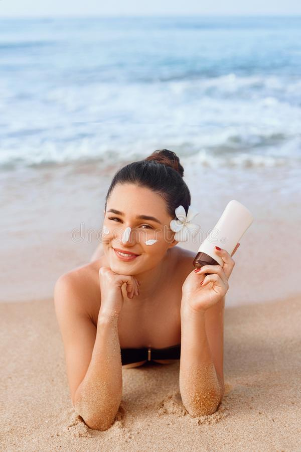 Γυναίκα ομορφιάς στα μπουκάλια εκμετάλλευσης μπικινιών Sunscreen στα χέρια της Skincare Ένα όμορφο θηλυκό που εφαρμόζει την κρέμα στοκ εικόνα