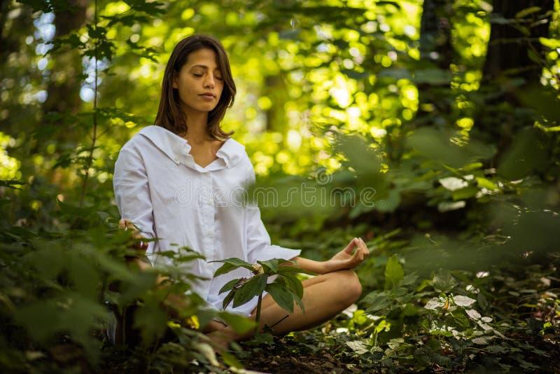 Γυναίκα ομορφιάς στη θέση γιόγκας φύσης στοκ εικόνα