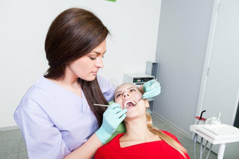 Γυναίκα οδοντιάτρων που εξετάζει τα τέλεια άσπρη δόντια ή την οδοντοστοιχία στοκ φωτογραφία