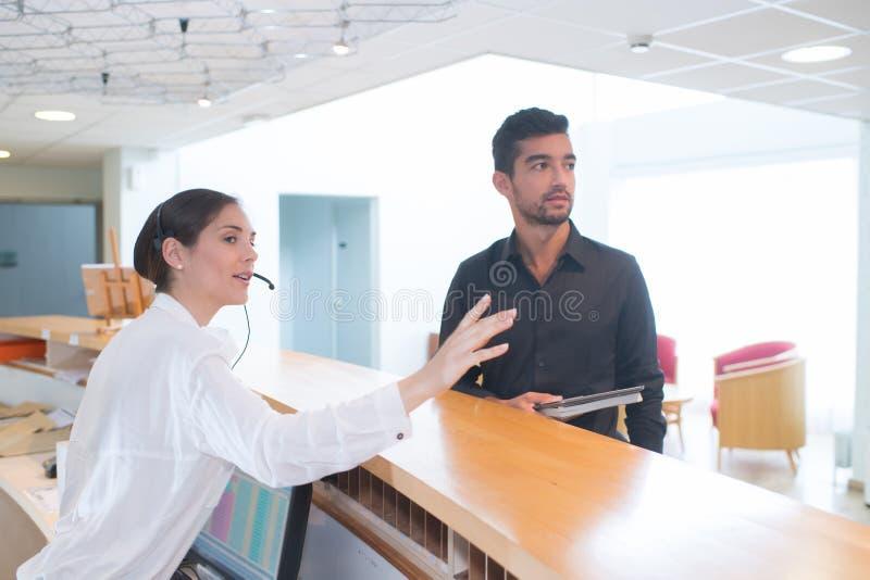 Γυναίκα πίσω από το διοικητή γραφείων υποδοχής με τον επισκέπτη πελατών στοκ εικόνες