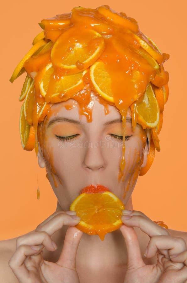 Γυναίκα πορτρέτου στην ΚΑΠ των πορτοκαλιών στοκ φωτογραφία