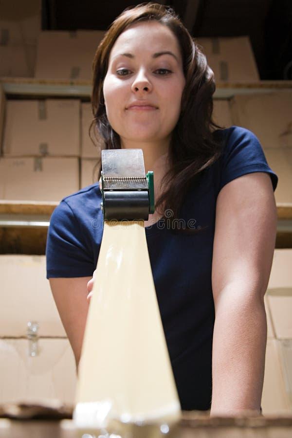 Γυναίκα που δένει επάνω το κιβώτιο με ταινία στοκ εικόνα