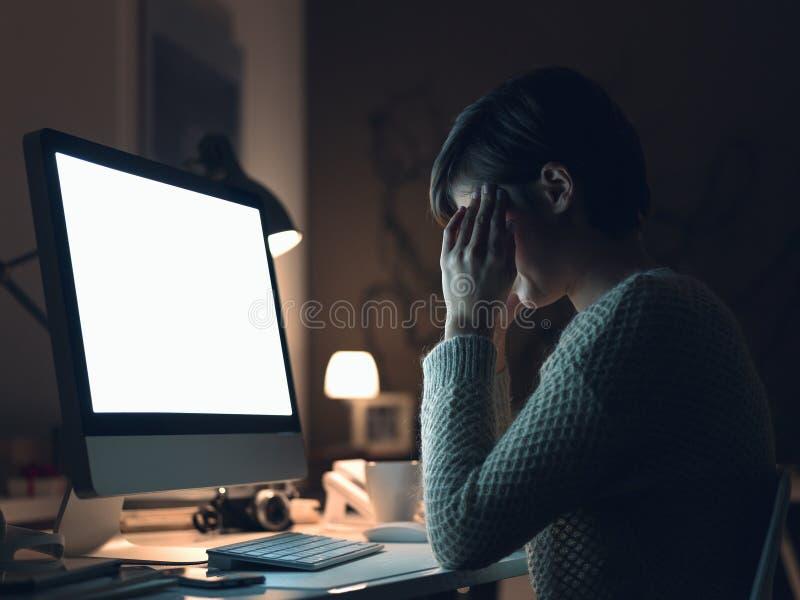 Γυναίκα που έχει έναν πονοκέφαλο αργά τη νύχτα στοκ φωτογραφία
