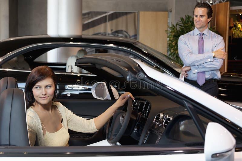Γυναίκα που έχει ένα τεστ δοκιμής ενώ πωλητής που στέκεται εκτός από το αυτοκίνητο στοκ φωτογραφίες