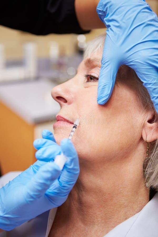 Γυναίκα που έχει την επεξεργασία Botox στην κλινική ομορφιάς στοκ εικόνες