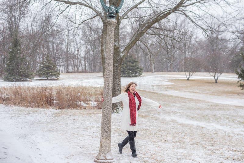 Γυναίκα που έχει τη διασκέδαση που ταλαντεύεται γύρω από τη θέση λαμπτήρων στο πάρκο ενώ το φρέσκο s στοκ εικόνες