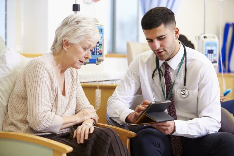 Γυναίκα που έχει τη χημειοθεραπεία με το γιατρό που χρησιμοποιεί την ψηφιακή ταμπλέτα στοκ εικόνα