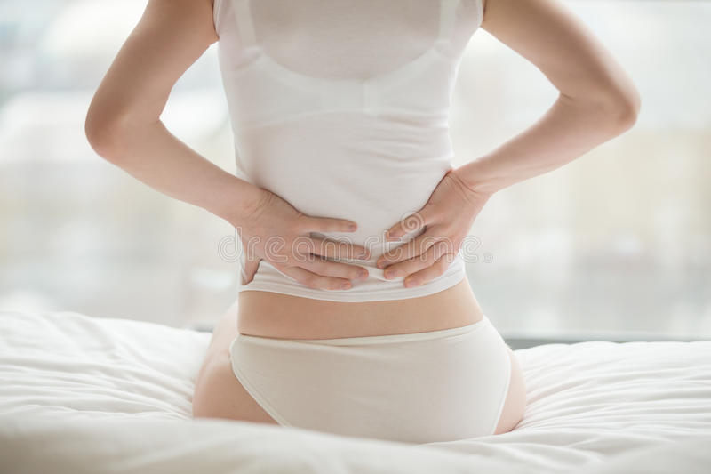 Γυναίκα που έχει τον πόνο στην πλάτη στοκ φωτογραφία