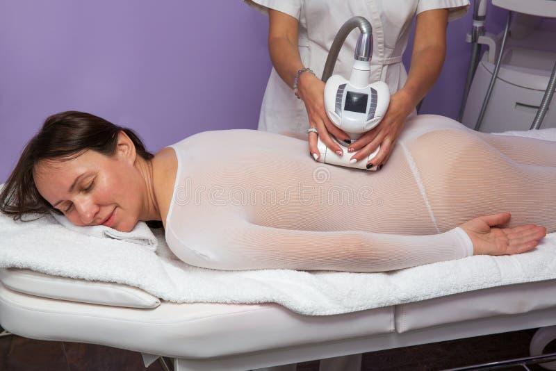 Γυναίκα που έχει το αντι μασάζ cellulite με τις συσκευές στοκ φωτογραφία