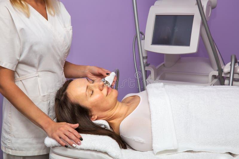 Γυναίκα που έχει το αντι μασάζ cellulite στο πρόσωπό της με το θεράποντα στοκ φωτογραφία με δικαίωμα ελεύθερης χρήσης