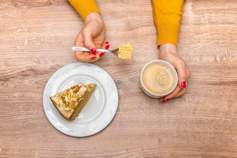 Γυναίκα που έχει το γλυκό κέικ και τον καυτό καφέ στο σπίτι στοκ εικόνες