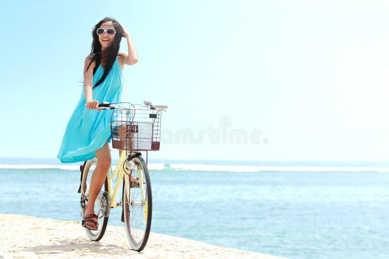 Γυναίκα που έχει το οδηγώντας ποδήλατο διασκέδασης στην παραλία στοκ φωτογραφία