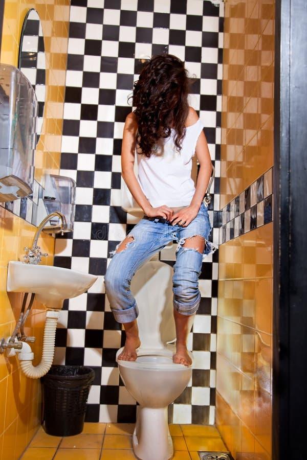 Γυναίκα που έχει το πρόβλημα με το κάθισμα τουαλετών στοκ φωτογραφία