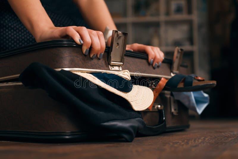Γυναίκα που έχει το πρόβλημα με το κλείσιμο μιας βαλίτσας στοκ εικόνες