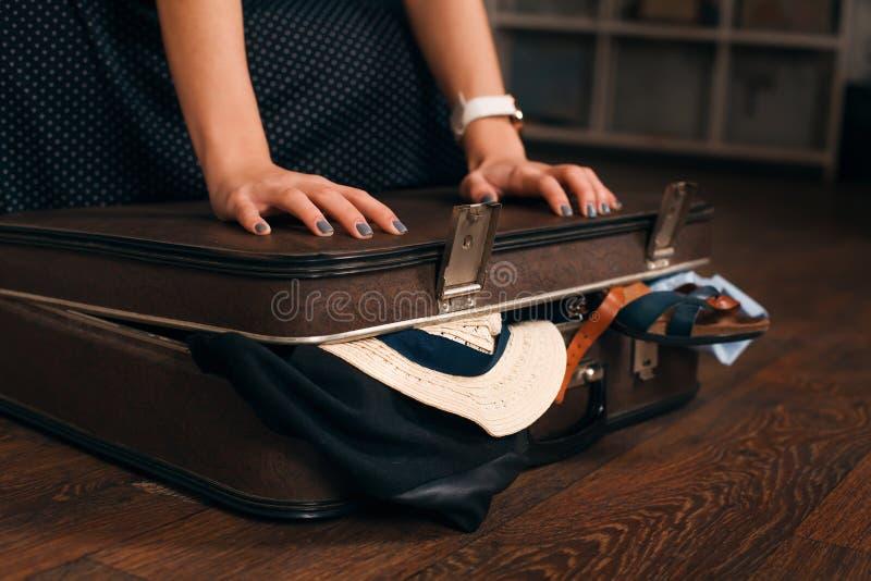 Γυναίκα που έχει το πρόβλημα με το κλείσιμο μιας βαλίτσας στοκ φωτογραφίες