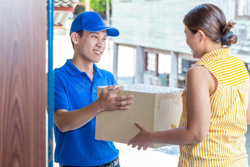 Γυναίκα που δέχεται μια παράδοση των κουτιών από χαρτόνι από deliveryman στοκ φωτογραφία με δικαίωμα ελεύθερης χρήσης