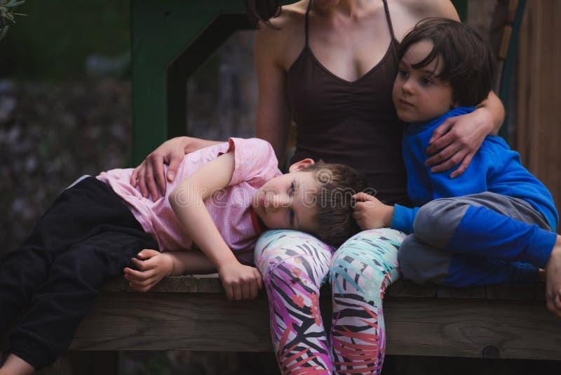 Γυναίκα που αγκαλιάζει τα παιδιά στο πεζούλι ενός ξύλινου σπιτιού στοκ φωτογραφία με δικαίωμα ελεύθερης χρήσης
