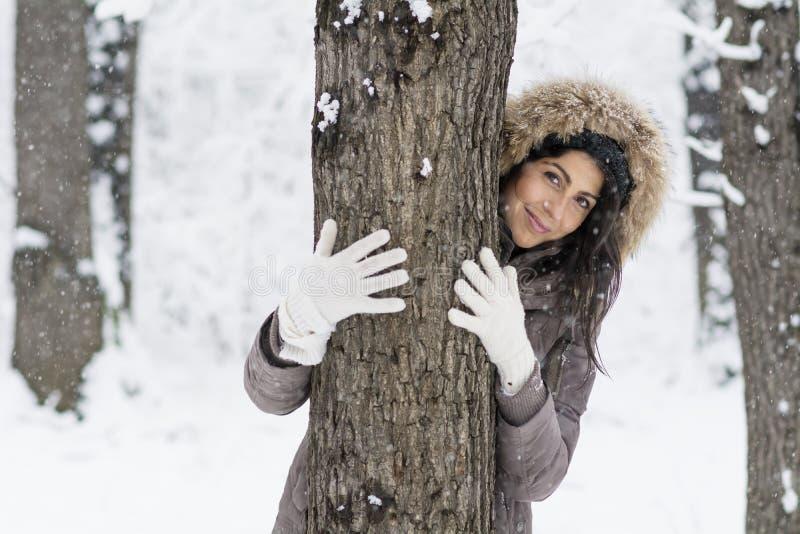 Γυναίκα που αγκαλιάζει ένα δέντρο στο χειμερινό δάσος φύση αγάπης στοκ φωτογραφία