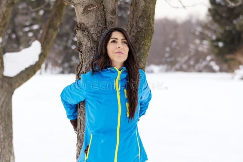 Γυναίκα που αγκαλιάζει ένα δέντρο στο χειμερινό δάσος φύση αγάπης στοκ εικόνες με δικαίωμα ελεύθερης χρήσης