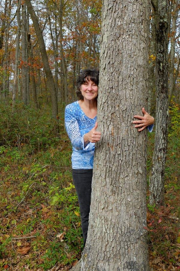 Γυναίκα που αγκαλιάζει το δέντρο στοκ εικόνες με δικαίωμα ελεύθερης χρήσης