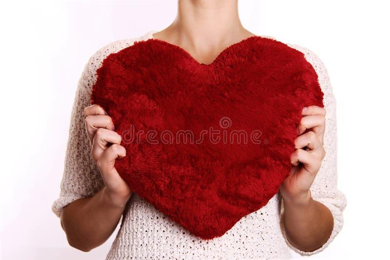 Γυναίκα που αγκαλιάζει το καρδιά-διαμορφωμένο μαξιλάρι στοκ φωτογραφία