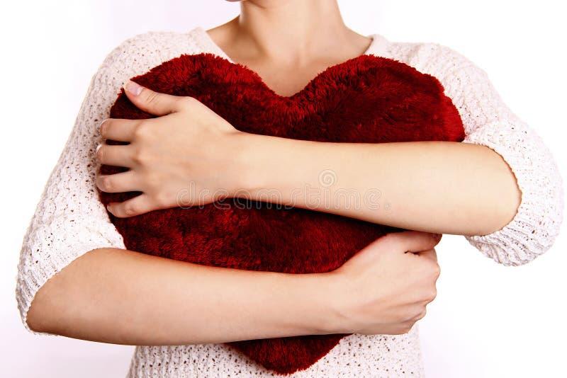 Γυναίκα που αγκαλιάζει το καρδιά-διαμορφωμένο μαξιλάρι στοκ φωτογραφία με δικαίωμα ελεύθερης χρήσης