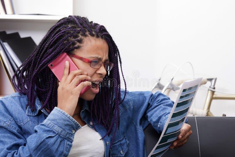 Γυναίκα που αγοράζει στο σπίτι από κινητό στοκ φωτογραφία με δικαίωμα ελεύθερης χρήσης