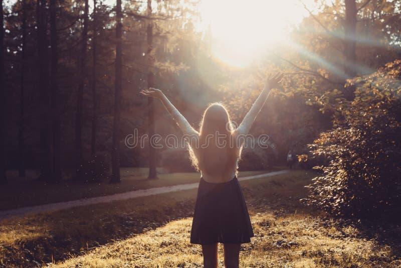 Γυναίκα που αισθάνεται ελεύθερη στο ηλιοβασίλεμα Σκιαγραφία των όπλων διάδοσης γυναικών με τους αντίχειρές της επάνω, που στέκετα στοκ εικόνες