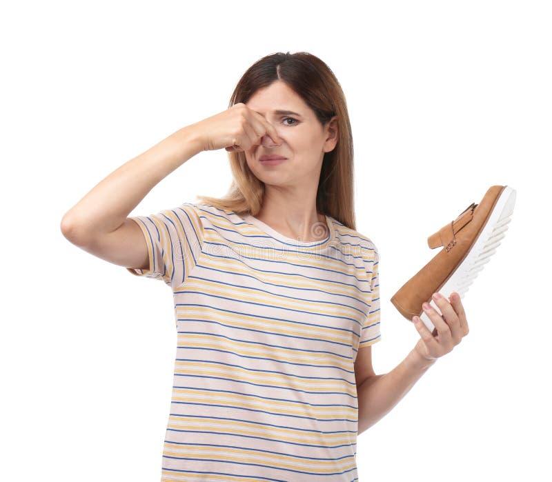 Γυναίκα που αισθάνεται την κακή μυρωδιά από το παπούτσι στοκ εικόνες