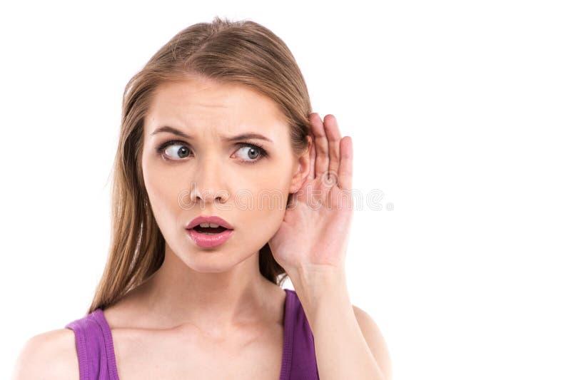 Γυναίκα που ακούει με το χέρι της σε ένα αυτί που απομονώνεται πέρα από το άσπρο υπόβαθρο στοκ εικόνες