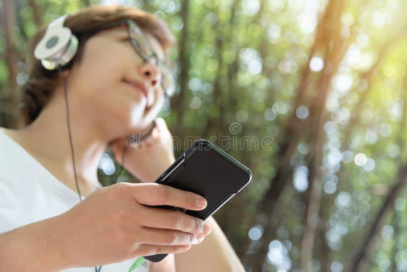 Γυναίκα που ακούει τη μουσική με το ακουστικό και το έξυπνο τηλέφωνο στοκ φωτογραφία με δικαίωμα ελεύθερης χρήσης