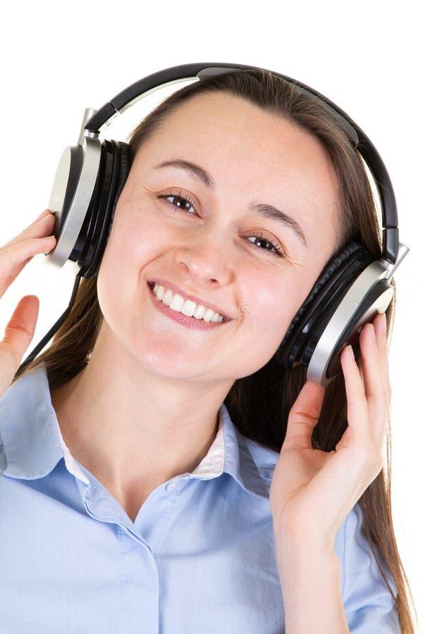 Γυναίκα που ακούει τη μουσική στα ακουστικά που απολαμβάνουν και που τραγουδούν στοκ εικόνα