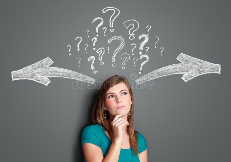 Γυναίκα που λαμβάνει μια απόφαση με τα βέλη και το ερωτηματικό επάνω από την στοκ εικόνες