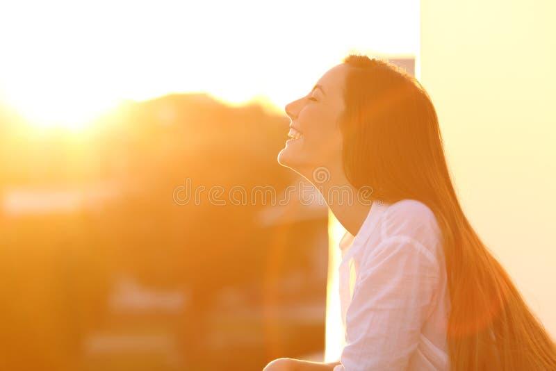 Γυναίκα που αναπνέει στο ηλιοβασίλεμα σε ένα μπαλκόνι στοκ εικόνα