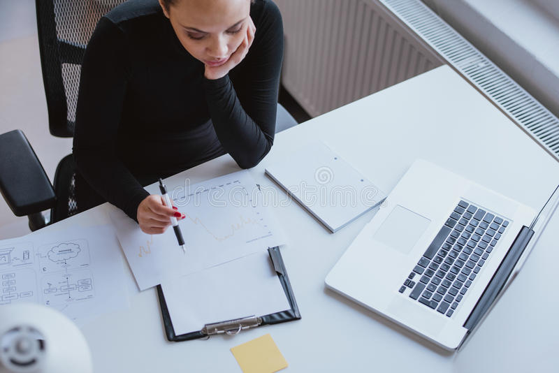 Γυναίκα που αναλύει το διάγραμμα της προόδου εργασίας και του προγραμματισμού στοκ φωτογραφίες με δικαίωμα ελεύθερης χρήσης