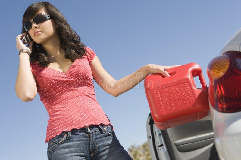 Γυναίκα που ανεφοδιάζει σε καύσιμα το αυτοκίνητό της μιλώντας στο τηλέφωνο κυττάρων στοκ φωτογραφίες με δικαίωμα ελεύθερης χρήσης