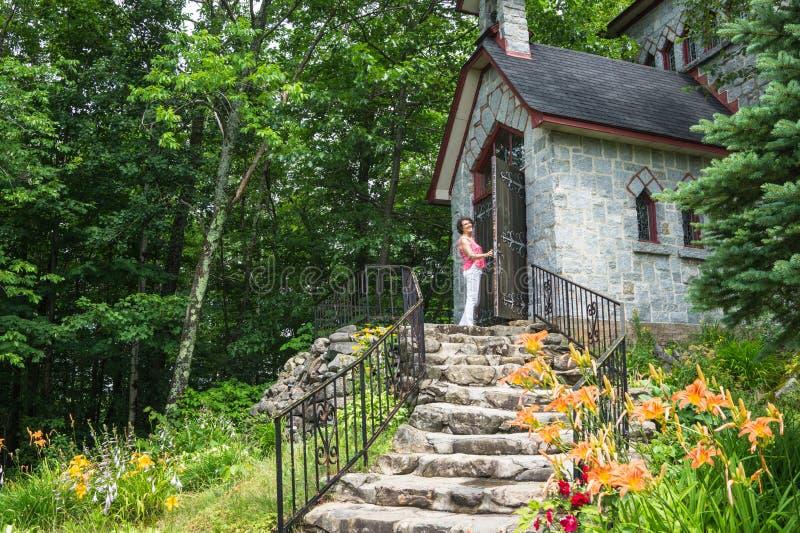 Γυναίκα που ανοίγει τη βαριά ξύλινη πόρτα στο σπίτι πετρών στοκ φωτογραφία