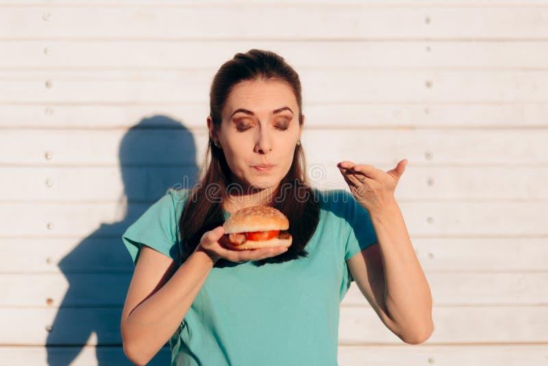 Γυναίκα που αξιολογεί την ποιότητα Burger από τη μυρωδιά του στοκ εικόνες