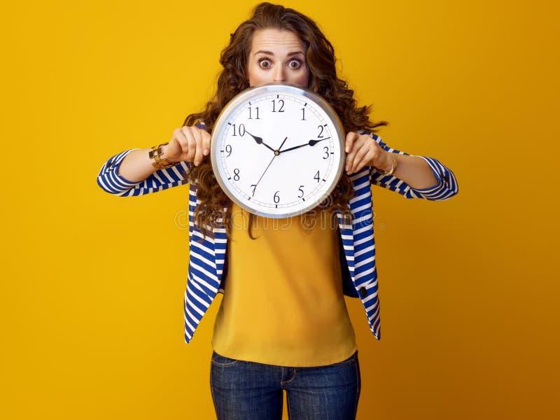 Γυναίκα που απομονώνεται στο κίτρινο κρύψιμο υποβάθρου πίσω από το ρολόι στοκ εικόνα με δικαίωμα ελεύθερης χρήσης