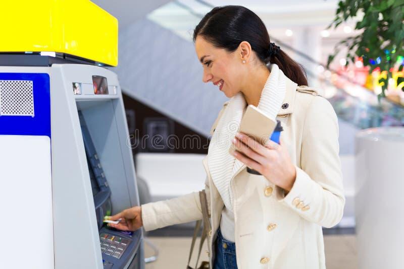 Γυναίκα που αποσύρει τα μετρητά στο ATM στοκ εικόνα με δικαίωμα ελεύθερης χρήσης