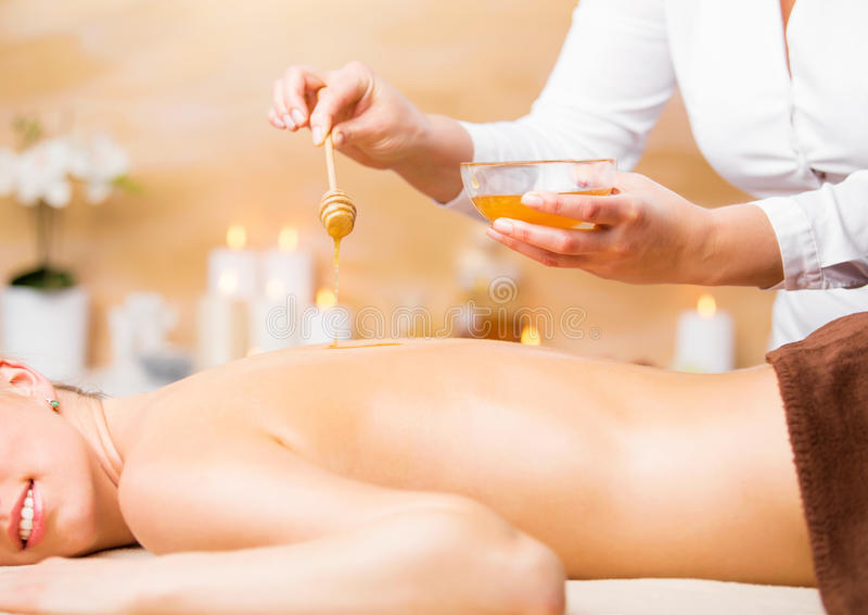 Γυναίκα που απολαμβάνει την επεξεργασία SPA με το μέλι στοκ φωτογραφίες