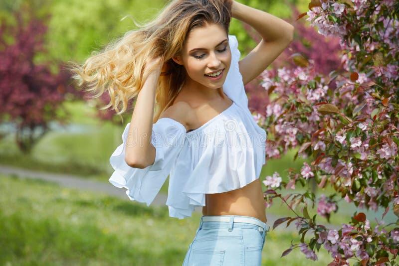 Γυναίκα που απολαμβάνει τη μυρωδιά σε έναν ανθίζοντας κήπο άνοιξη στοκ φωτογραφίες με δικαίωμα ελεύθερης χρήσης