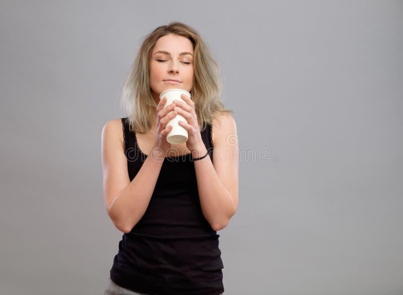 Γυναίκα που απολαμβάνει το ζεστό ποτό στο μίας χρήσης φλυτζάνι εγγράφου στοκ φωτογραφίες