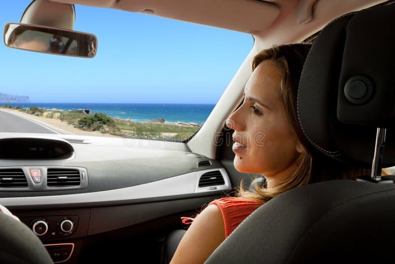 Γυναίκα που απολαμβάνει το νέο αυτοκίνητο με το σύζυγο στοκ φωτογραφία