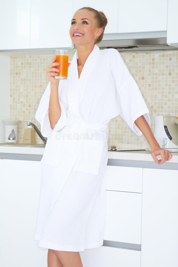 Γυναίκα που απολαμβάνει το φρέσκο χυμό από πορτοκάλι για το πρόγευμα στοκ φωτογραφίες με δικαίωμα ελεύθερης χρήσης