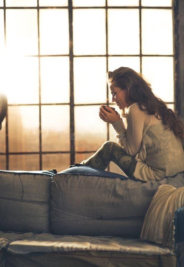 Γυναίκα που απολαμβάνει το φλυτζάνι του ποτού στο διαμέρισμα σοφιτών στοκ φωτογραφία